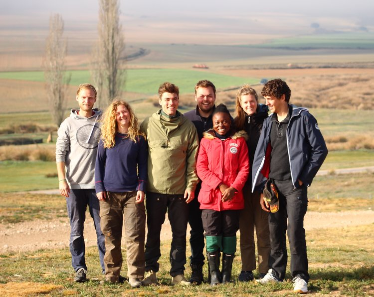 Group picture of young people standing on a field with trees in the background