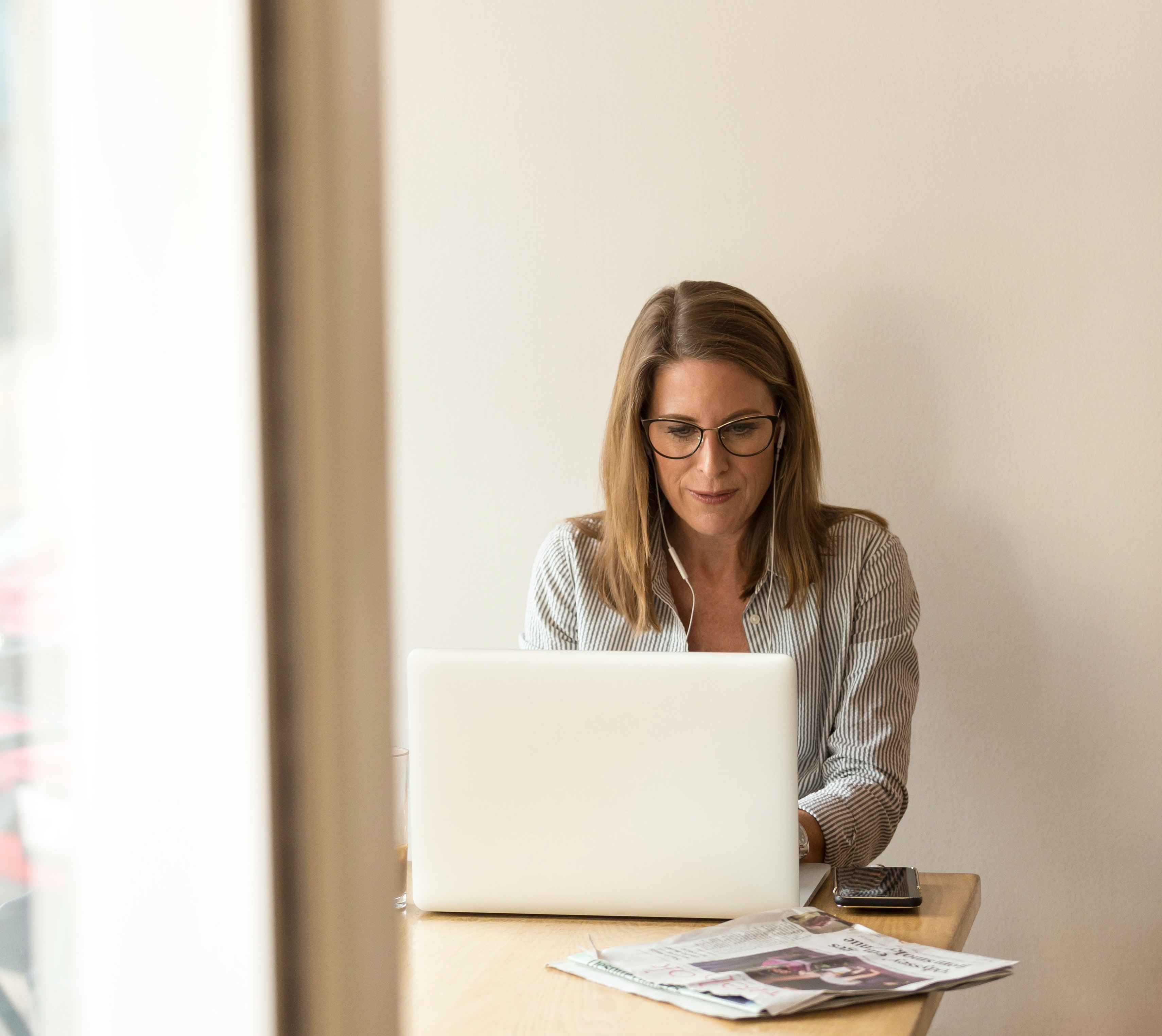 Woman sitting in front of laptop creme